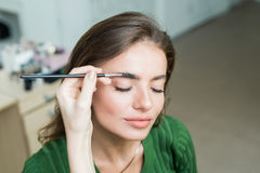 Woman paints the eyebrows royalty free stock photography