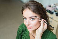 Woman paints the eyebrows stock image