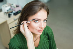 Woman paints the eyebrows royalty free stock image