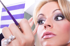 Woman  paints face with makeup Royalty Free Stock Images