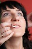 Woman paints face with makeup Stock Photos