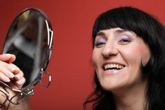 Woman paints face with makeup Stock Image
