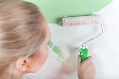 Woman paints green wall Royalty Free Stock Photos