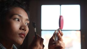 Woman paints her eyebrows stock footage