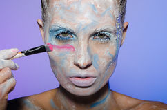 Woman paints her face with colors Royalty Free Stock Photo