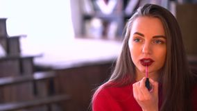 Woman paints her lips with lipstick. Make up applying, lipgloss, lipstick. Portrait of young attractive girl rouging her stock video