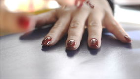 Woman paints her nails on hand with red lacquer stock footage