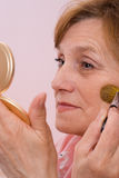 Woman paints his face and looks in the mirror Royalty Free Stock Image