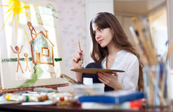 Woman paints home of dreams Royalty Free Stock Image
