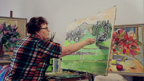 A woman paints a landscape with oil paints with a palette and brush. stock video