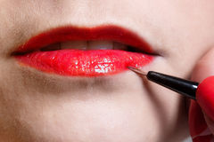 Woman paints lips Royalty Free Stock Images