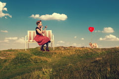 Woman  paints lips with lipstick sitting on a couch in nature. Royalty Free Stock Images