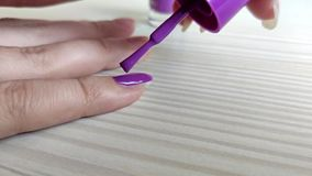 Woman paints nails with purple nail polish stock video