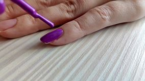 Woman paints nails with purple nail polish stock footage