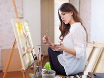Woman paints with oil colors on easel Stock Image