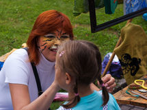 Woman paints a paint mask on the girl's face Royalty Free Stock Photo