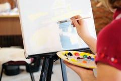 Woman paints a picture. Image of a Woman paints a picture stock image