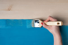 Woman paints the table. Woman hand painter paints the wooden table Royalty Free Stock Images