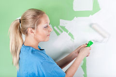 Woman paints the wall Stock Photos