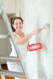 Woman paints wall with brush at home Stock Photos