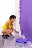 Woman paints wall by purple roller Royalty Free Stock Photo