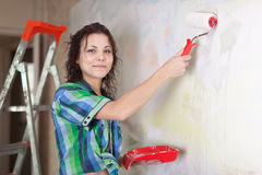 Woman paints wall with roller Stock Images