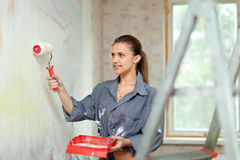 Woman paints wall with roller Stock Photo