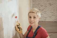 Woman paints the wall Royalty Free Stock Photo