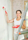 Woman paints wall with roller Stock Image
