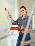 Woman paints wall with roller at home Royalty Free Stock Images