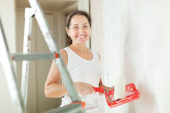 Woman paints wall with roller at home Royalty Free Stock Image