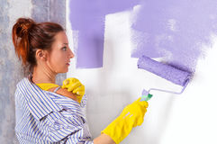 Woman paints white wall with purple paint roller Stock Image