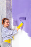 Woman paints white wall with purple paint roller Stock Photos