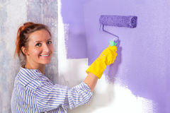 Woman paints white wall with purple paint roller Royalty Free Stock Photography