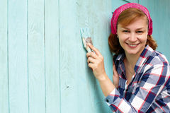 Woman paints a wooden wall of blue paint. Idea of repair Royalty Free Stock Images