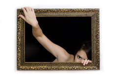 Woman in a paiting frame. Young woman in a painting frame on a wall tries to exit, she is peeking out Royalty Free Stock Photo