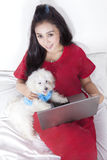 Woman with pajama and dog using laptop. Unique perspective of young woman sitting on the bed while wearing pajama and using laptop with her dog royalty free stock photography