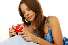 Woman in pajama seated on a sofa Stock Photo