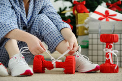 Woman in pajamas and athletic shoes unties the bow on the dumbbe Stock Image