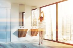 Woman in pajamas in bathroom with shower. Young woman in pajamas standing in modern bathroom with white walls, wooden floor, two wooden sinks and shower with stock photo
