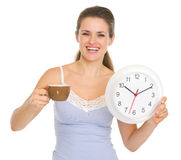 Woman in pajamas with cup of coffee and clock Stock Photography