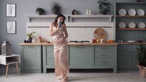 Woman in pajamas dancing and singing in kitchen at home stock video