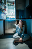 Woman in pajamas eating on floor next to fridge at night Stock Image