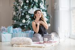 Woman in pajamas having breakfast at floor. Morning on New Year`s Eve. Christmas concept stock photography