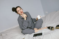 Woman in pajamas holding coffee cup on her bed Stock Images