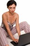 Woman in pajamas on laptop Stock Photos
