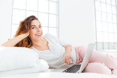 Woman in pajamas lying on the bed with laptop computer Stock Images