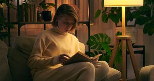 Woman reading a book on sofa at night