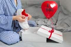 Woman in pajamas received a gift of sports shoes. Valentine`s Da Stock Photo