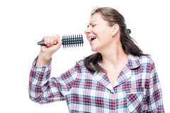 Woman in pajamas singing in hairbrush before going to bed. On white background stock photos